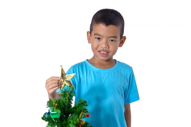 Glückliches asiatisches kind, das goldstern für dekoration weihnachtsbaum hält. weihnachten oder ein frohes neues jahr