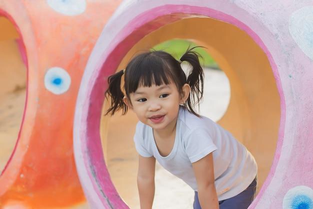 Glückliches asiatisches kind, das mit dem spielzeug am parkspielplatz spielt. lern- und kinderkonzept.
