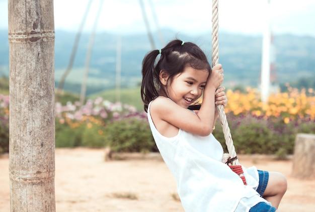 Glückliches asiatisches kind des kleinen kindes, das spaß hat, auf hölzernen schwingen im spielplatz am garten zu spielen