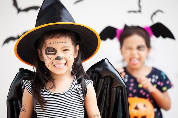 Glückliches asiatisches kind des kleinen kindes in den kostümen und in make-up, die spaß auf halloween-feier haben