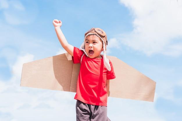 Glückliches asiatisches kind kleines jungenlächeln tragen pilotenhut und schutzbrille spielen spielzeugkarton flugzeugflügel fliegen