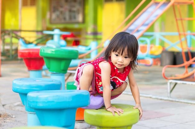 Glückliches asiatisches kindermädchen, das das spielzeug am spielplatz klettert und spielt.