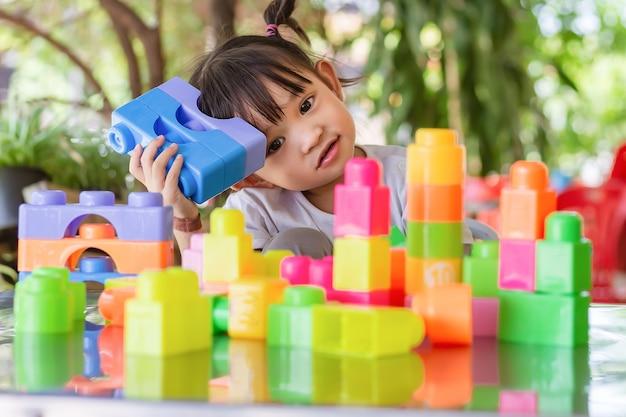 Glückliches asiatisches kindermädchen, das die plastikblockspielzeuge spielt. lern- und bildungskonzept. lächelndes kleines baby.