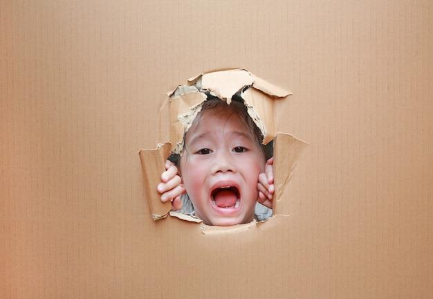 Glückliches asiatisches kindermädchen, das durch loch auf pappe mit kopienraum schaut.