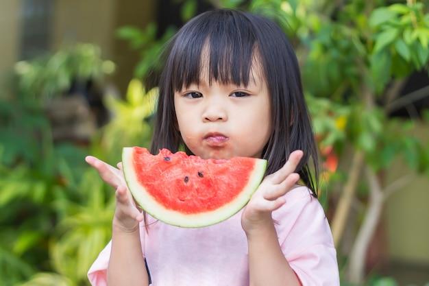 Glückliches asiatisches kindermädchen, das ein stück wassermelone isst und beißt.