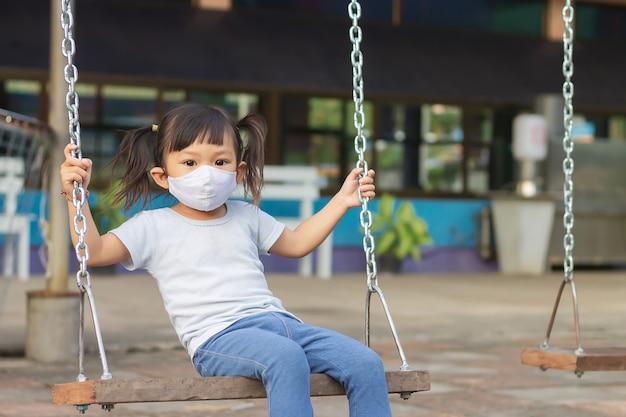 Glückliches asiatisches kindermädchen, das eine stoffgesichtsmaske trägt, wenn sie ein schaukelsitzspielzeug am parkspielplatz spielt.