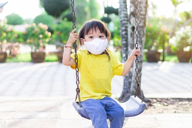 Glückliches asiatisches kindermädchen, das eine stoffgesichtsmaske trägt, wenn sie ein spielzeug am spielplatz spielt.