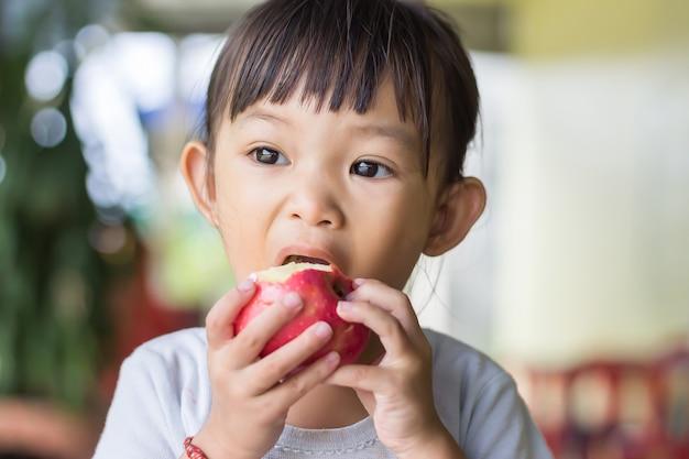 Glückliches asiatisches kindermädchen, das einen roten apfel isst und beißt. genieße den moment des essens.