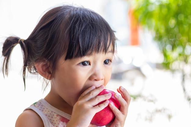 Glückliches asiatisches kindermädchen, das einen roten apfel isst und beißt.
