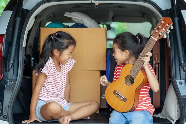 Glückliches asiatisches kindermädchen, das gitarre spielt und ein lied mit ihrer schwester in einem autokofferraum singt