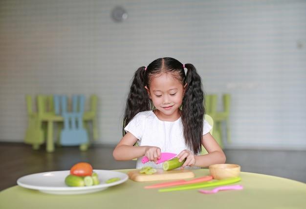 Glückliches asiatisches kindermädchen, das gurke auf hackendem brett schneidet