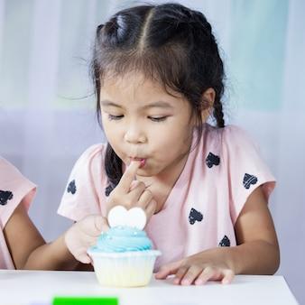 Glückliches asiatisches kindermädchen, das köstlichen blauen kleinen kuchen isst