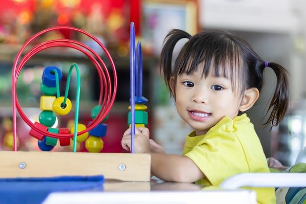 Glückliches asiatisches kindermädchen, das mit vielen spielzeugen im raum zu hause spielt.