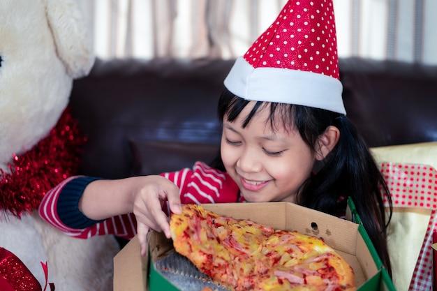 Glückliches asiatisches kindermädchen, das pizza in dem raum isst, der für weihnachten verziert wird