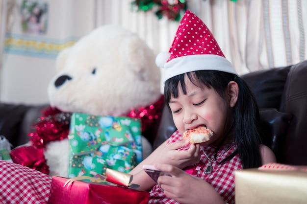 Glückliches asiatisches kindermädchen, das pizza isst und smartphone in dem raum verwendet, der für weihnachten verziert wird