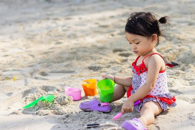 Glückliches asiatisches kindermädchen, das sand am strand am meer spielt. in der sommersaison.