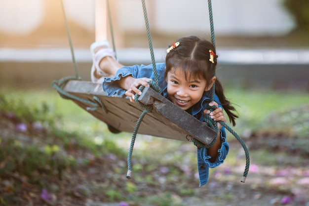 Glückliches asiatisches kindermädchen, das spaß hat, auf hölzernem schwingen im spielplatz am park zu spielen