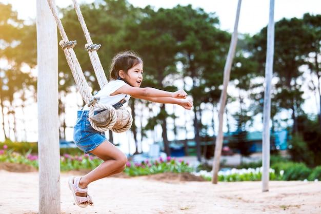 Glückliches asiatisches kindermädchen, das spaß hat, auf hölzernem schwingen im spielplatz mit schöner natur zu spielen