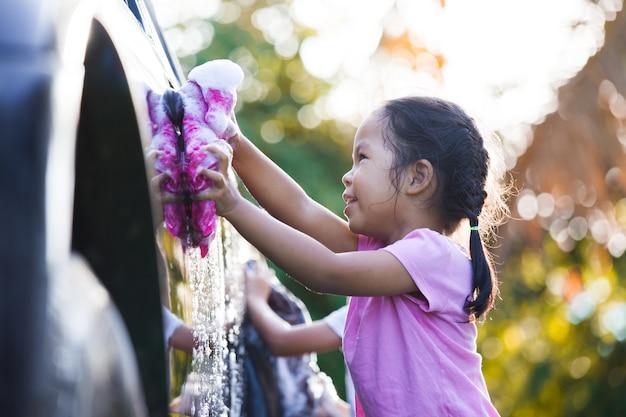 Glückliches asiatisches kindermädchen, das spaß hat, waschendes auto des elternteils mit sonnenlicht zu helfen