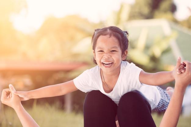 Glückliches asiatisches kindermädchen, das spaß lacht und hat, mit ihrer mutter im park zu spielen