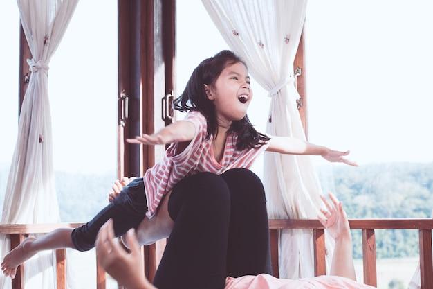 Glückliches asiatisches kindermädchen, das spaß lacht und hat, mit ihrer mutter im raum zu spielen