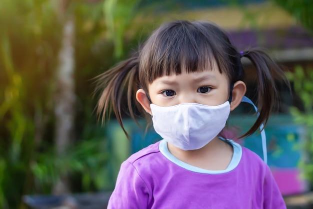 Glückliches asiatisches kindermädchen, das stoffmaske lächelt und trägt. sie spielt auf dem spielplatz.