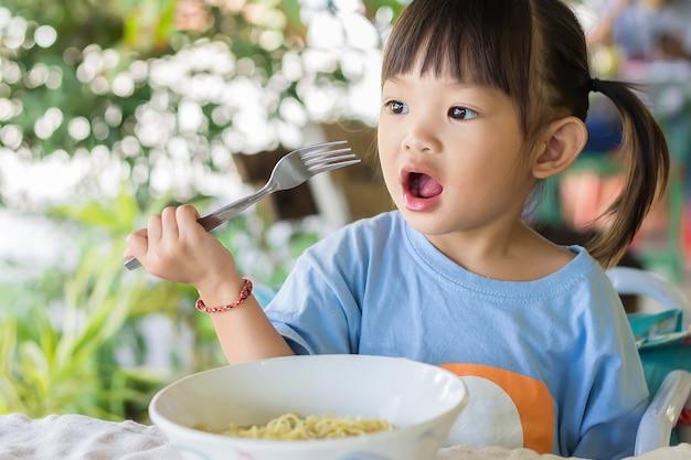 Glückliches asiatisches kindermädchen genießt, einige nudeln allein zu essen.