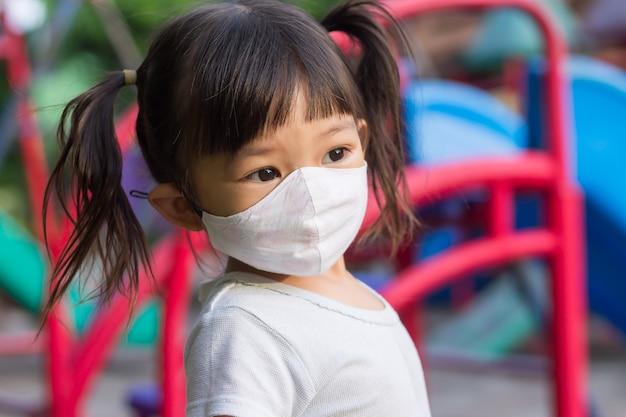 Glückliches asiatisches kindermädchen lächelnd und stoffmaske tragend.