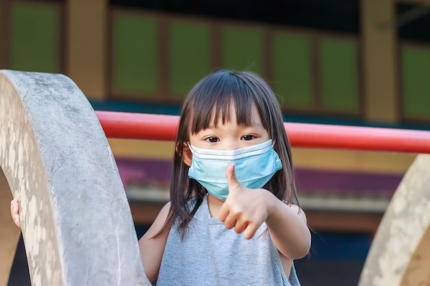 Glückliches asiatisches kindermädchen lächelnd und tragen stoffmaske. sie spielt mit slider bar spielzeug auf dem spielplatz,