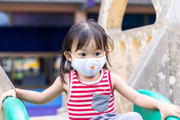 Glückliches asiatisches kindermädchen lächelt und trägt stoffmaske.