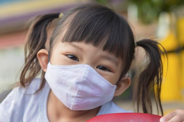 Glückliches asiatisches kindermädchen lächelt und trägt stoffmaske