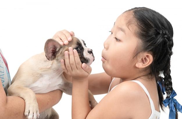 Glückliches asiatisches kindermädchenspiel mit französischer bulldogge