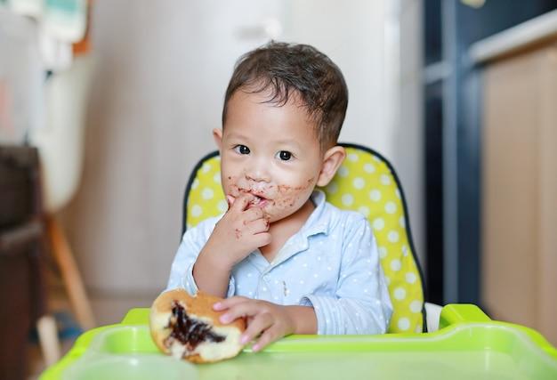 Glückliches asiatisches kleines baby, das auf dem kinderstuhl isst innenbrot mit angefüllter schokolade sitzt