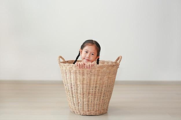 Glückliches asiatisches kleines kindermädchen, das im rattankorb im zimmer zu hause sitzt