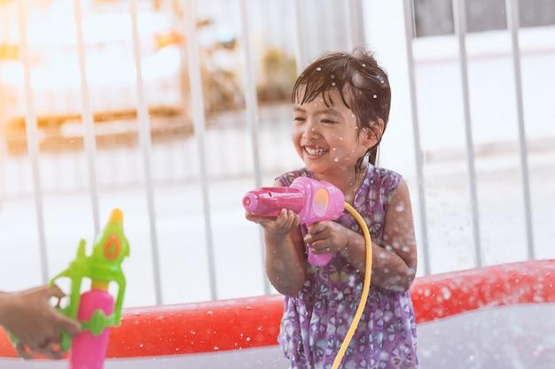 Glückliches asiatisches kleines kindermädchen, das spaß hat, wasser mit wasserwerfer und in songkran fest zu spielen