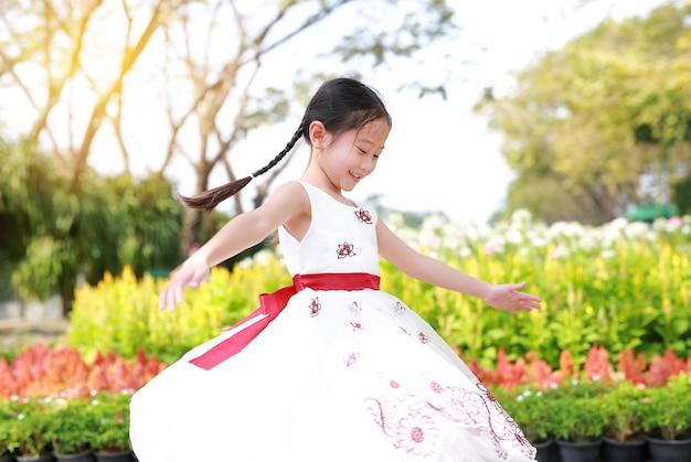 Glückliches asiatisches kleines kindermädchen tanzt und hat spaß im frischen blumengarten. kinder spielen im park im freien.
