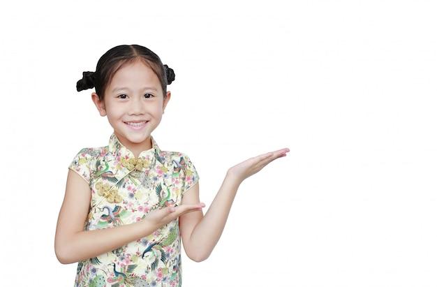 Glückliches asiatisches kleines mädchen, das cheongsam mit lächelnder und grüßender geste trägt, die für glückliches chinesisches neujahr feiert, lokalisiert mit kopienraum für ihren text.