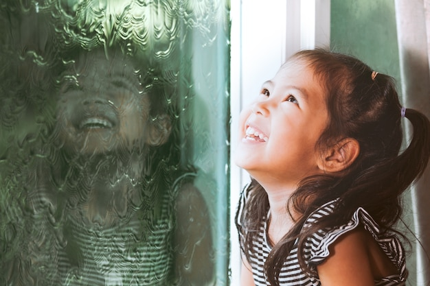 Glückliches asiatisches kleines mädchen, das draußen durch das fenster am regnerischen tag schaut
