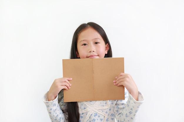 Glückliches asiatisches kleines mädchen, das offenes braunes buch mit blick in die kamera über weißem studiohintergrund hält