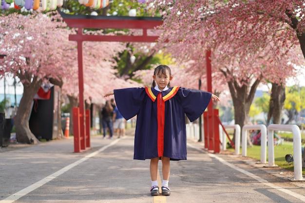 Glückliches asiatisches kleines mädchen im abschluss. unter dem blühenden sakura-baum