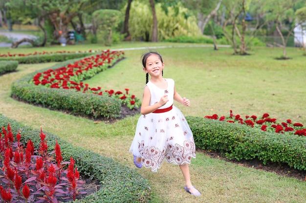 Glückliches asiatisches kleines mädchen im weißen kleid, das läuft und spaß im blumengarten hat.