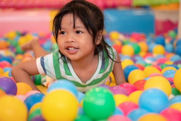 Glückliches asiatisches mädchen (4 jahre alt), das kleine bunte bälle in der poolkugel spielt. das spielen ist das beste lernen für kinder.