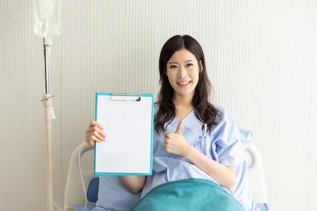 Glückliches asiatisches mädchen auf einem krankenhausbett mit einem leeren papier