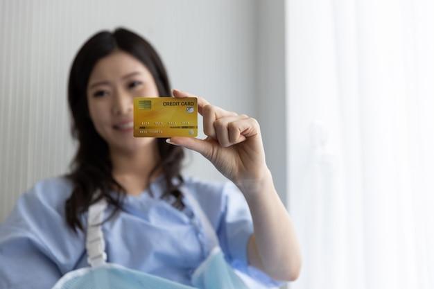 Glückliches asiatisches mädchen auf einem krankenhausbett mit einer kreditkarte