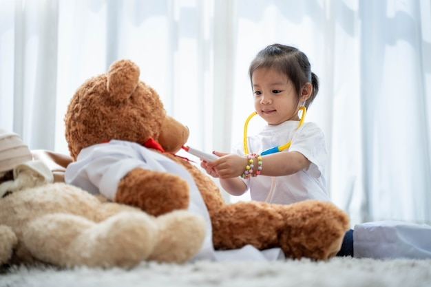 Glückliches asiatisches mädchen, das arzt oder krankenschwester mit einem teddybär spielt.