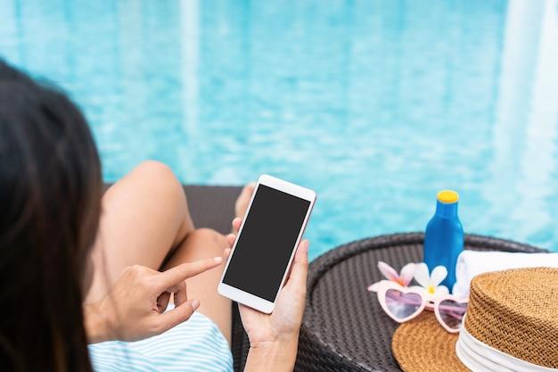 Glückliches asiatisches mädchen, das badeanzug trägt, der auf sonnenliege liegt und smartphone verwendet, das am pool mit hut entspannt