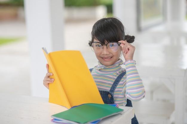 Glückliches asiatisches mädchen, das ein buch auf dem tisch liest