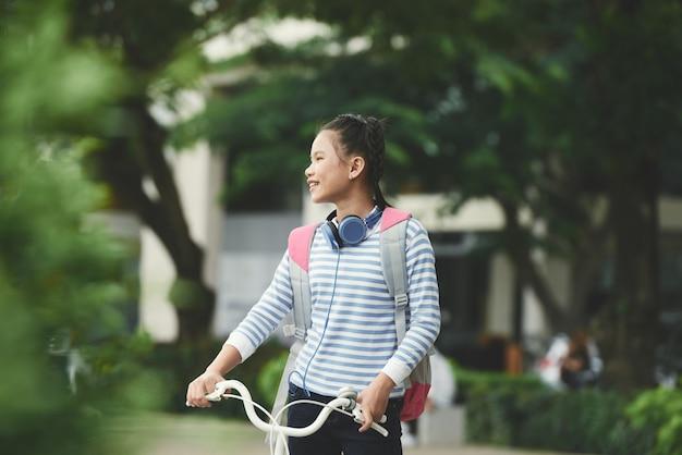 Glückliches asiatisches mädchen, das fahrrad hält und herum im park schaut