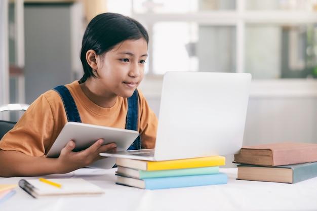 Glückliches asiatisches mädchen, das online zu hause lernt