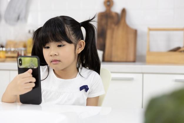 Glückliches asiatisches mädchen genießen smartphone